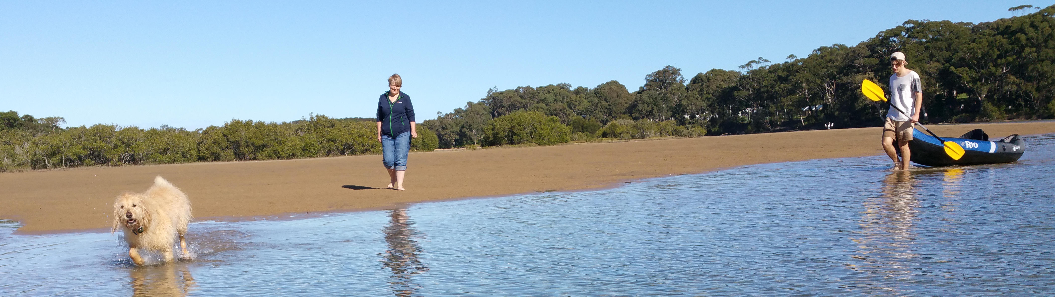 Dog, Carmel and Ash walk over a sand bar