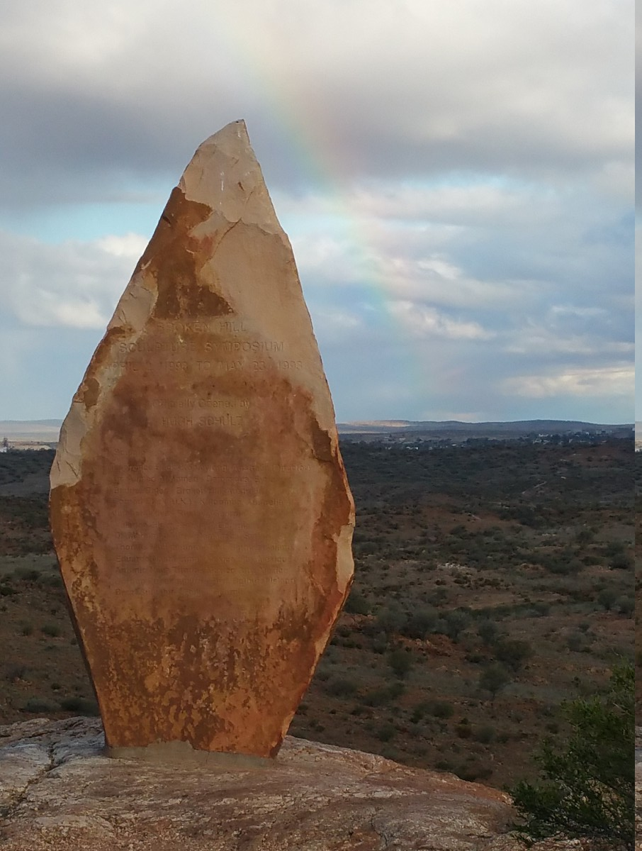 A faint rainbow to the right of a sculpture